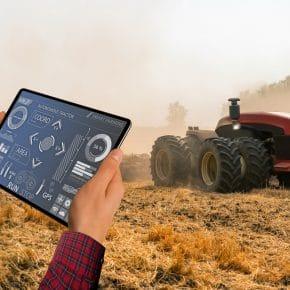 A farmer with digital tablet controls an autonomous tractor