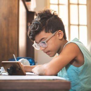 Kid on phone doing schoolwork