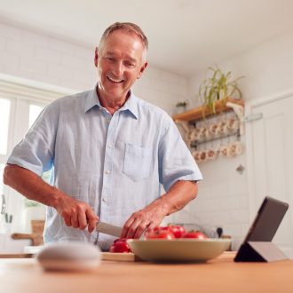 Retired Man Making Meal In Kitchen Asking Smart Speaker