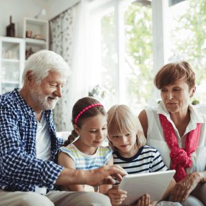 Grandparent on mobile device with grandkids.