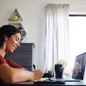 Lady making a list in front of laptop.