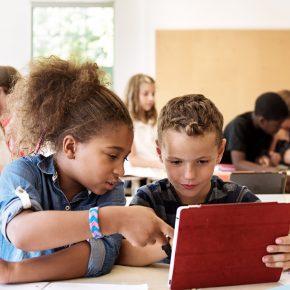 School kids in class using a digital tablet