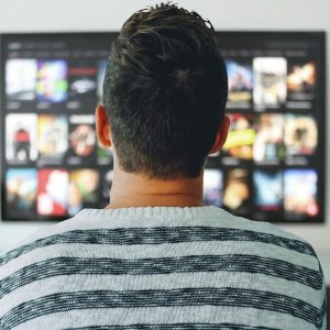 Man watching TV, AT&T to launch AVOD similar to HBO Max